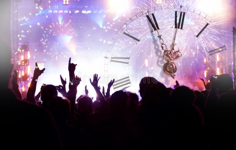 Ρολόι κοντά στα μεσάνυχτα, τα πυροτεχνήματα και το πλήθος που περιμένουν το νέο yea στοκ εικόνες