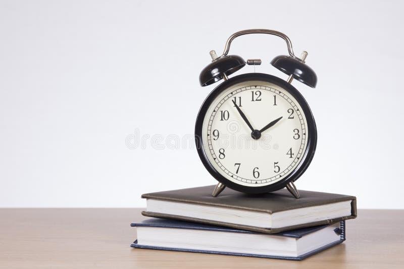 Ρολόι συναγερμών που στέκεται στα βιβλία στοκ εικόνες με δικαίωμα ελεύθερης χρήσης