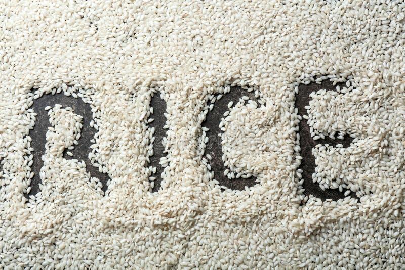 ΡΥΖΙ λέξης που γίνεται με τα σιτάρια στο γκρίζο υπόβαθρο στοκ φωτογραφία με δικαίωμα ελεύθερης χρήσης