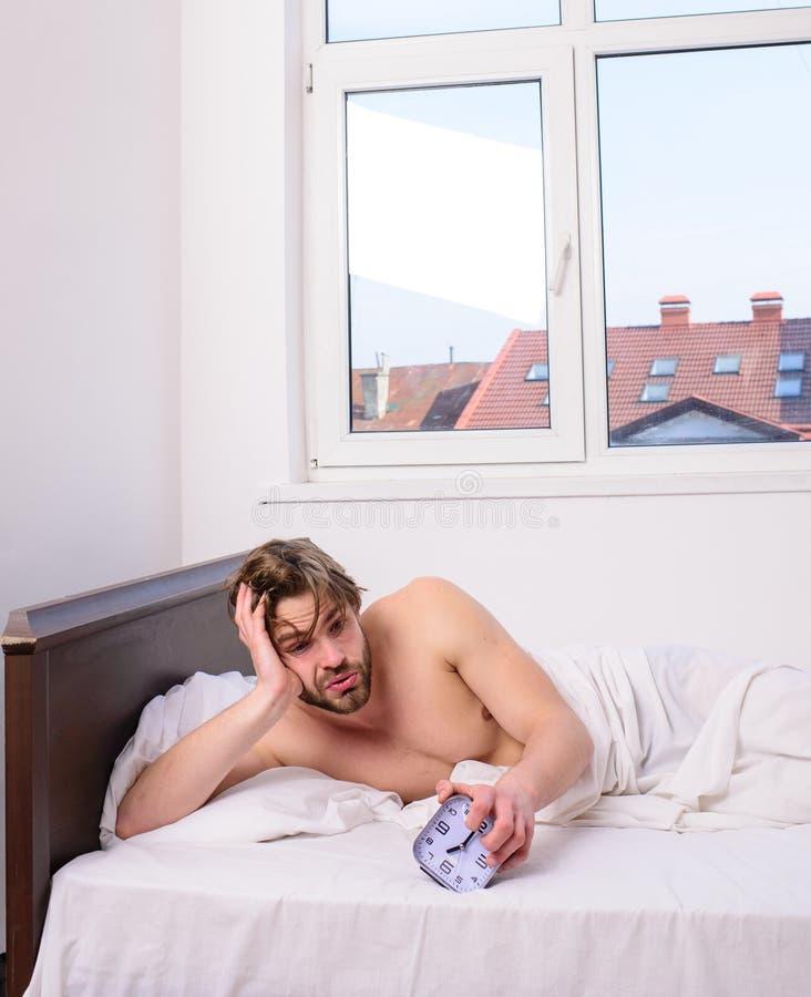 Ρυθμίστε το ρολόι bodys σας Συνήθεια καθεστώτος ύπνου Το άτομο αξύριστο βάζει το ξυπνητήρι λαβής κρεβατιών Ίδια ώρα για ύπνο προγ στοκ εικόνες με δικαίωμα ελεύθερης χρήσης