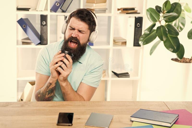 Ρυθμός ζωής γραφείων Κανονική ημέρα γραφείων Τα γενειοφόρα ακουστικά τύπων ατόμων κάθονται το γραφείο ακούνε μουσική τραγουδούν τ στοκ εικόνες