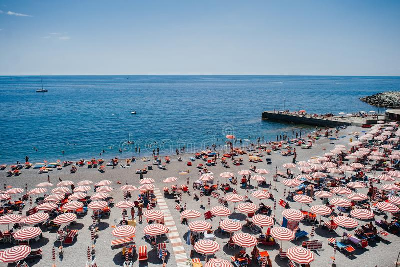 Ρυθμός των κόκκινων ομπρελών και των τουριστών σε μια ηλιόλουστη παραλία στη Γένοβα, Ιταλία στοκ εικόνα