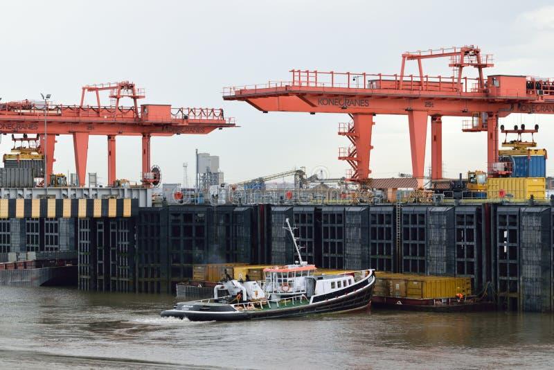 Ρυμουλκό παράλληλα με την αποβάθρα στον ποταμό Τάμεσης UK με δύο γερανούς ατσάλινων σκελετών στο υπόβαθρο στοκ φωτογραφία
