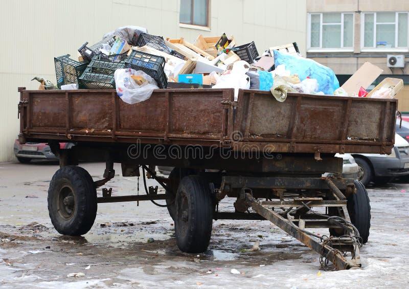 Ρυμουλκό τρακτέρ που φορτώνεται με τα οικιακά απορρίματα στοκ εικόνα με δικαίωμα ελεύθερης χρήσης