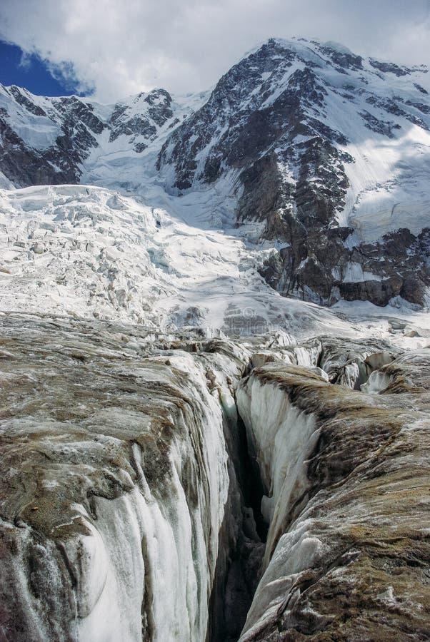 ρωγμή στον παγετώνα και τα χιονώδη βουνά, Ρωσική Ομοσπονδία, Καύκασος, στοκ εικόνα