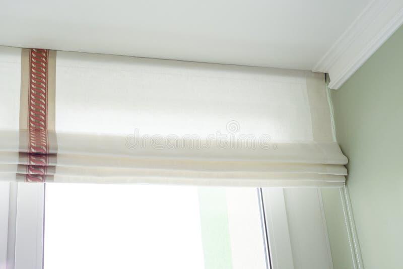 Ρωμαϊκές κουρτίνες στο εσωτερικό Από ένα φυσικό ελαφρύ λινό, με τη διακοσμητική πλεξούδα στοκ φωτογραφία με δικαίωμα ελεύθερης χρήσης
