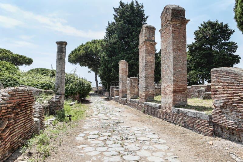 Ρωμαϊκή άποψη οδών αυτοκρατοριών με τις καταστροφές και ρωμαϊκές στήλες και χαρακτηριστικός δρόμος κυβόλινθων σε Ostia Antica - τ στοκ φωτογραφία με δικαίωμα ελεύθερης χρήσης