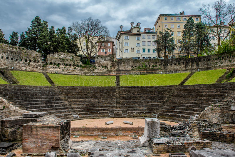 Ρωμαϊκό θέατρο στην Τεργέστη με μια πόλη στο υπόβαθρο στοκ εικόνα