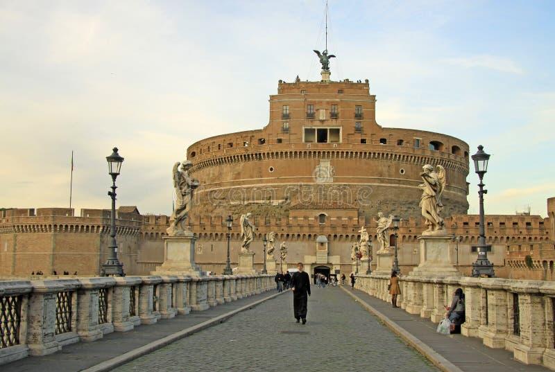 ΡΩΜΗ, ΙΤΑΛΙΑ - 20 ΔΕΚΕΜΒΡΊΟΥ 2012: Νέος εκκλησιαστικός και άλλοι άνθρωποι στη γέφυρα Castel Sant'Angelo στη Ρώμη, Ιταλία στοκ εικόνες