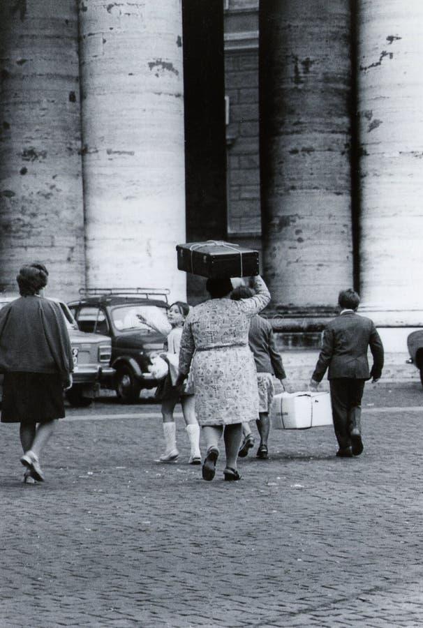 ΡΩΜΗ, ΙΤΑΛΙΑ, 1970 - μια οικογένεια των μεταναστών περπατά κοντά στην κιονοστοιχία του S Πλατεία του Peter με ένα κουτί από χαρτό στοκ φωτογραφία