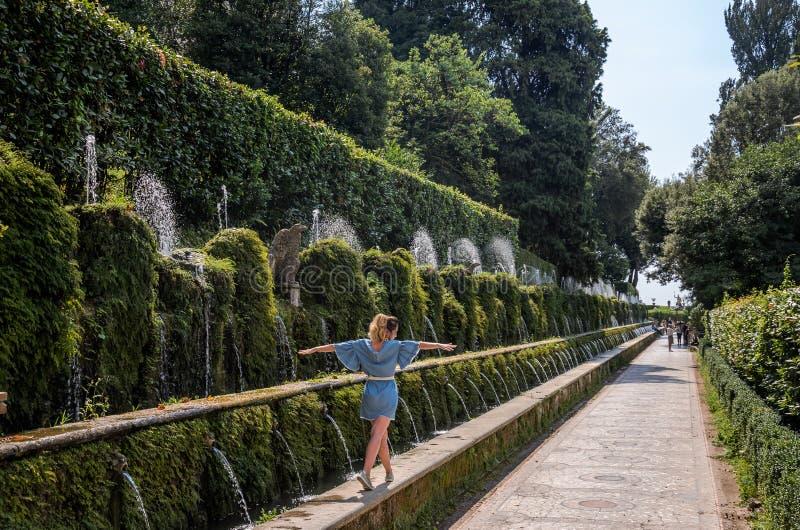 """ΡΩΜΗ, ΙΤΑΛΙΑ - ΤΟΝ ΑΎΓΟΥΣΤΟ ΤΟΥ 2018: Ένα νέο κορίτσι περπατά κατά μήκος της αλέας των εκατοντάδων των πηγών στη βίλα δ """"Este σε  στοκ φωτογραφία"""