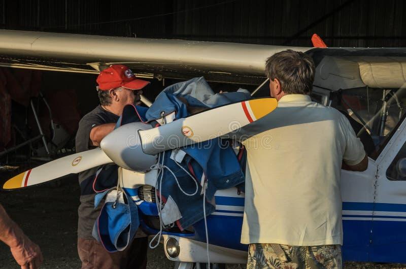 ΡΩΜΗ, ΙΤΑΛΙΑ - ΤΟΝ ΑΎΓΟΥΣΤΟ ΤΟΥ 2018: Δύο πιλότοι καλύπτουν την ελαφριά μηχανή τους με τα αεροσκάφη ηχούς Tecnam για το χώρο στάθ στοκ φωτογραφία με δικαίωμα ελεύθερης χρήσης