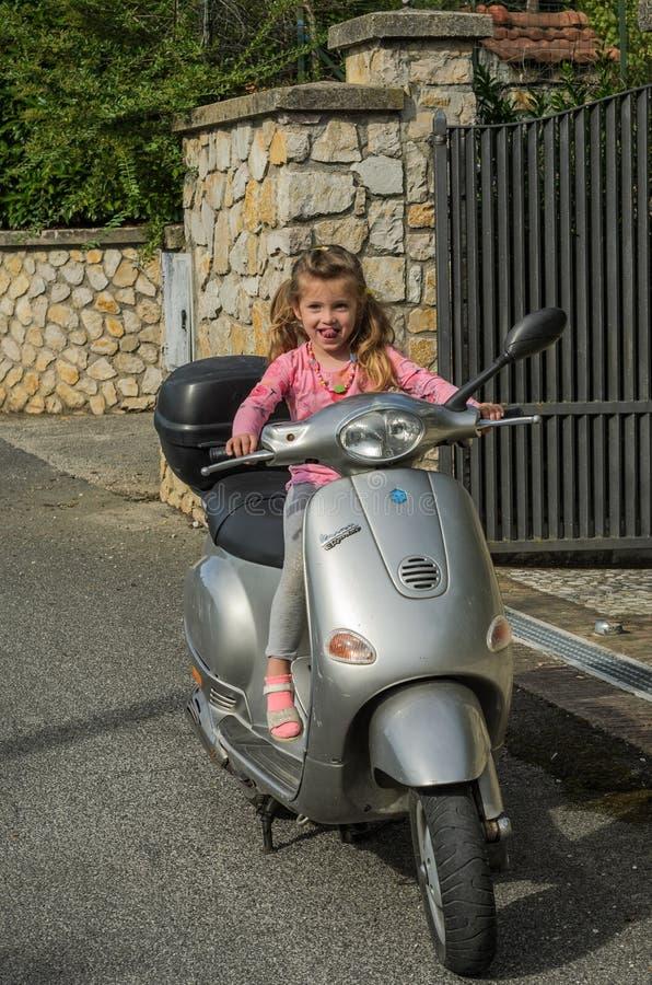 ΡΩΜΗ, ΙΤΑΛΙΑ - ΤΟΝ ΑΎΓΟΥΣΤΟ ΤΟΥ 2018: Λίγο όμορφο κορίτσι που οδηγεί ένα μηχανικό δίκυκλο Vespa στις παλαιές ιταλικές οδούς στοκ φωτογραφία με δικαίωμα ελεύθερης χρήσης