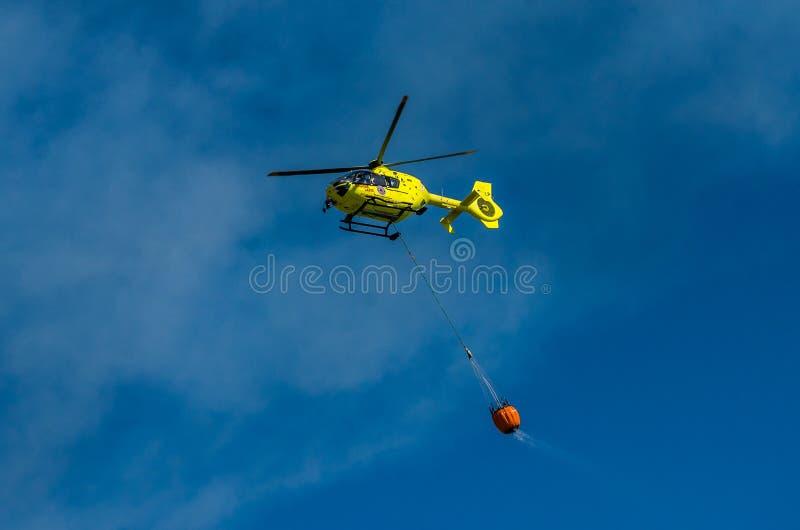 ΡΩΜΗ, ΙΤΑΛΙΑ - ΤΟΝ ΙΟΎΛΙΟ ΤΟΥ 2017: Ένα ελικόπτερο πυρκαγιάς παίρνει το νερό σε ένα καλάθι για την εξάλειψη μιας πυρκαγιάς στη Ty στοκ εικόνες