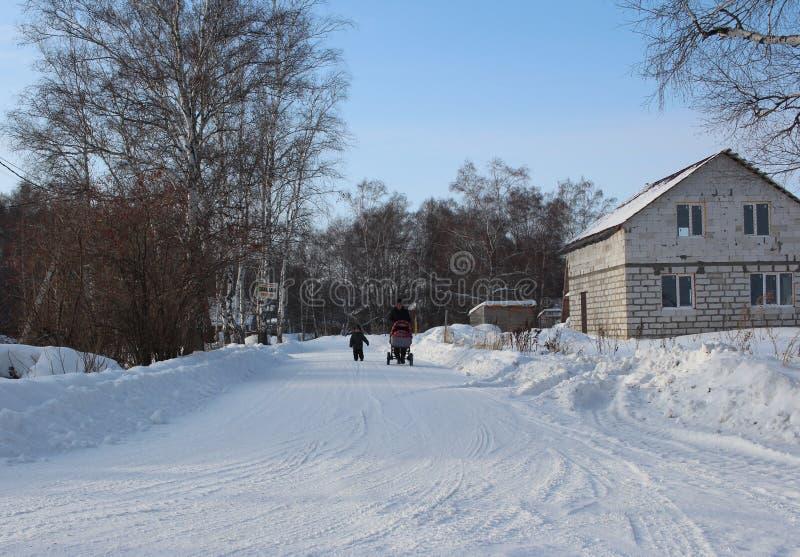 Ρωσία, Novosibirsk, στις 16 Ιανουαρίου 2019: μια γυναίκα κυλά μια μεταφορά μωρών στο δρόμο στο πάρκο περπατώντας με ένα μικρό παι στοκ εικόνα με δικαίωμα ελεύθερης χρήσης