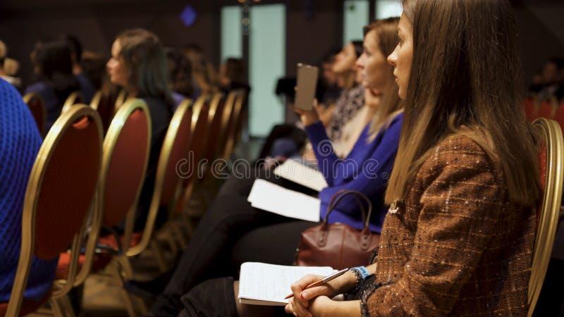 ΡΩΣΙΑ, ΜΟΣΧΑ - 13 ΑΠΡΙΛΊΟΥ 2019: Οι γυναίκες κάθονται στην επιχειρησιακή κατάρτιση με τα σημειωματάρια Τέχνη Οι όμορφες κυρίες κά στοκ εικόνα