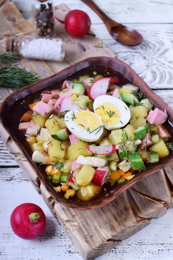 Ρωσική κρύα σούπα Okroshka με τα λαχανικά, το λουκάνικο, τα αυγά και kvass σε ένα ξύλινο κύπελλο στοκ εικόνα με δικαίωμα ελεύθερης χρήσης