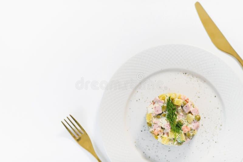 Ρωσική σαλάτα σε ένα άσπρο πιάτο με ένα χρυσό μαχαίρι και δίκρανο σε ένα άσπρο υπόβαθρο στοκ φωτογραφίες με δικαίωμα ελεύθερης χρήσης