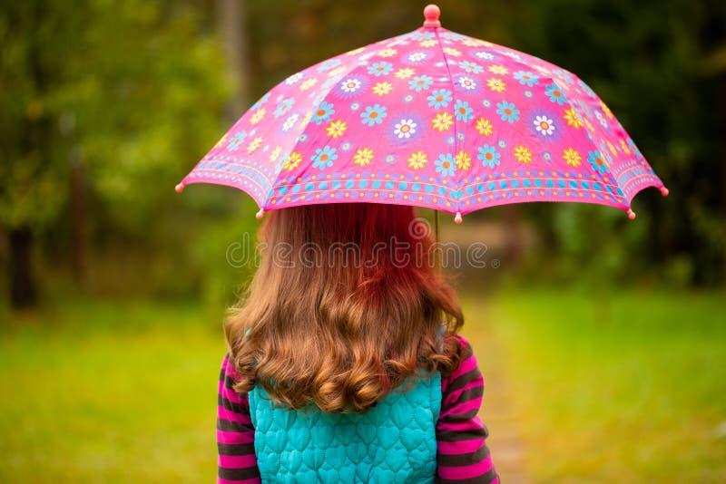Ρωσικό μικρό κορίτσι με την καφετιά τρίχα κάτω από την ομπρέλα στην ισοτιμία φθινοπώρου στοκ εικόνες