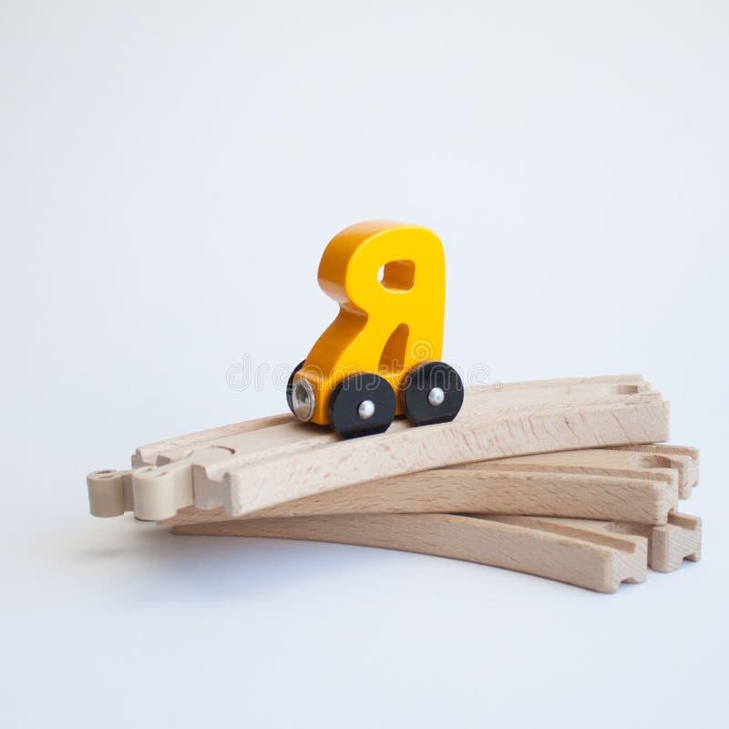 Ρωσικό ξύλινο αλφάβητο αυτοκινήτων τραίνων επιστολών Φωτεινό κίτρινο χρώμα στον ξύλινο σιδηρόδρομο ένα άσπρο υπόβαθρο Η πρόωρη εκ στοκ εικόνες με δικαίωμα ελεύθερης χρήσης