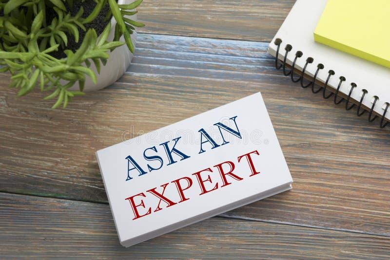 Ρωτήστε έναν εμπειρογνώμονα Επαγγελματική κάρτα με το μήνυμα, το σημειωματάριο και το λουλούδι Προμήθειες γραφείων στην άποψη επι στοκ φωτογραφίες με δικαίωμα ελεύθερης χρήσης