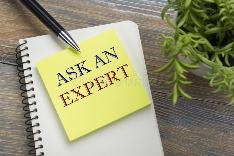 Ρωτήστε έναν εμπειρογνώμονα Σημειωματάριο με το μήνυμα, τη μάνδρα, την υπενθύμιση και το λουλούδι Προμήθειες γραφείων στην άποψη  στοκ εικόνα με δικαίωμα ελεύθερης χρήσης