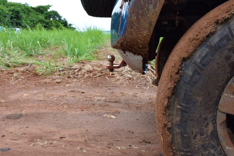 Ρόδα αυτοκινήτων από το δρόμο με τα μέρη του ρύπου και της έκτασης αυτοκίνητο στις αγροτικές περιοχές Σύγχρονο μπλε αυτοκίνητο πο στοκ εικόνα