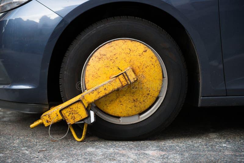 Ρόδα αυτοκινήτων που εμποδίζεται από την κλειδαριά ροδών επειδή παράνομη παραβίαση χώρων στάθμευσης στοκ φωτογραφία