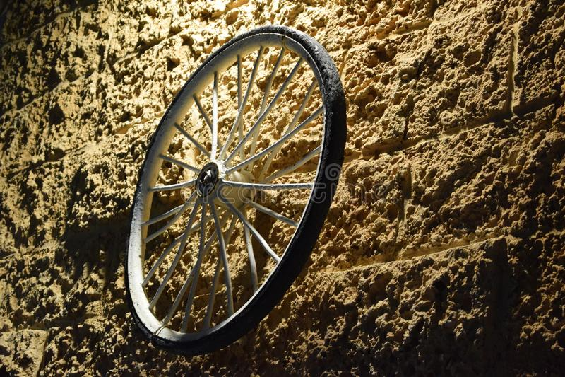 Ρόδα ποδηλάτων σε έναν κίτρινο τοίχο τη νύχτα Ισραήλ, Dimona, ` Mor `, 2018 τούβλου πετρών στοκ εικόνα με δικαίωμα ελεύθερης χρήσης
