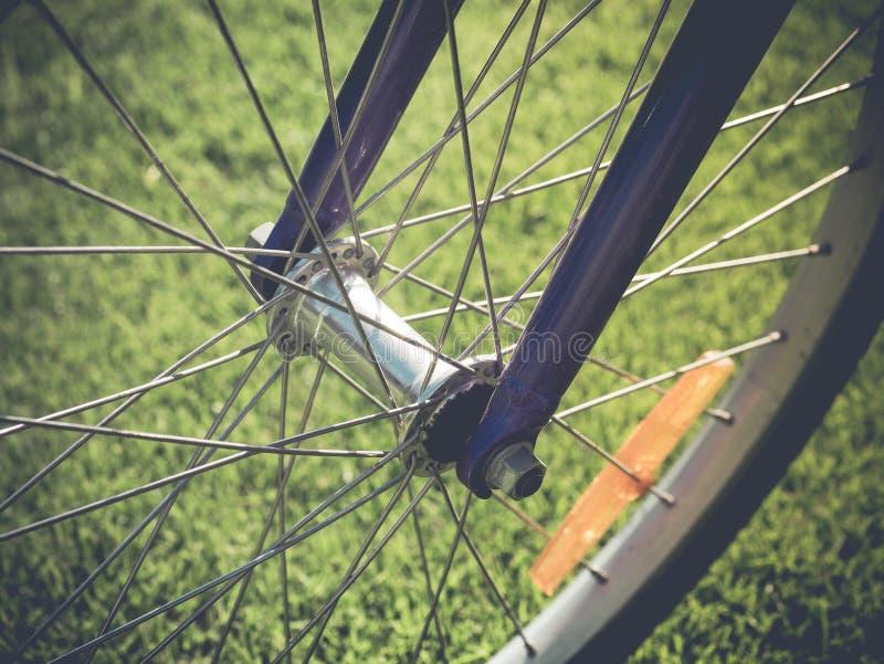 Ρόδα ποδηλάτων στον τομέα λιβαδιών θερινής πράσινο χλόης Κλείστε επάνω τη λεπτομέρεια στοκ φωτογραφία με δικαίωμα ελεύθερης χρήσης