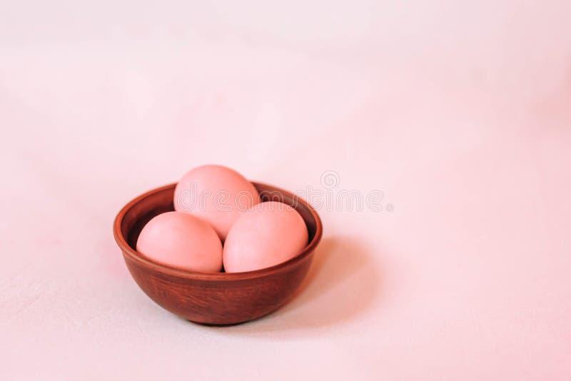 Ρόδινα αυγά Πάσχας σε ένα ξύλινο πιάτο σε ένα ρόδινο υπόβαθρο r στοκ φωτογραφίες