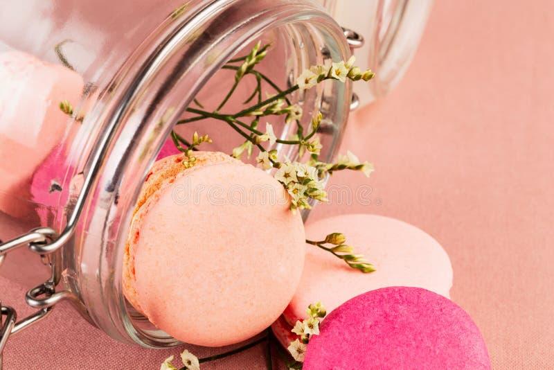 Ρόδινα γαλλικά macarons ή macaroons, που μειώνονται έξω ενός βάζου γυαλιού με τα μικρά κίτρινα λουλούδια πέρα από ένα ρόδινο υπόβ στοκ εικόνες με δικαίωμα ελεύθερης χρήσης