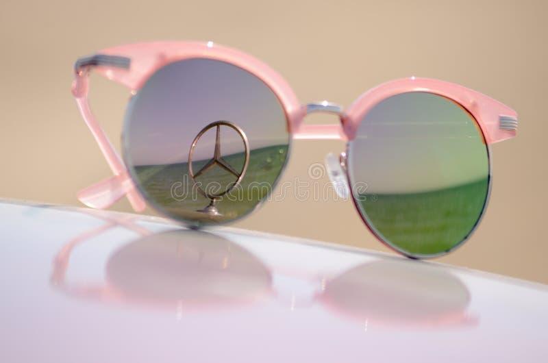 Ρόδινα γυαλιά ηλίου ενάντια στον ήλιο στην κουκούλα ενός αυτοκινήτου με ένα έμβλημα της Mercedes αστεριών στοκ φωτογραφίες