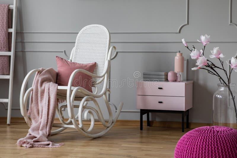 Ρόδινα κάλυμμα και μαξιλάρι κρητιδογραφιών στην άσπρη λικνίζοντας καρέκλα στο περίπλοκο δωμάτιο με το nightstand και τα λουλούδια στοκ φωτογραφία
