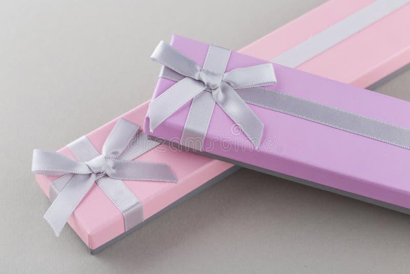 Ρόδινα και ιώδη κιβώτια δώρων με τα τόξα στο γκρίζο υπόβαθρο στοκ φωτογραφίες με δικαίωμα ελεύθερης χρήσης