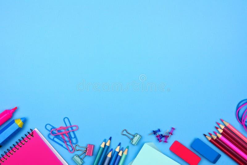 Ρόδινα και μπλε κατώτατα σύνορα σχολικών προμηθειών πέρα από ένα μπλε υπόβαθρο κρητιδογραφιών στοκ φωτογραφία