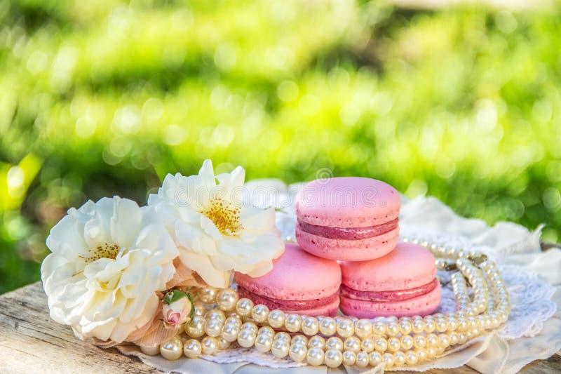 Ρόδινα λεπτά macaroons και άσπρα τριαντάφυλλα Γλυκά γυναικών ` s γλυκό δώρων επιδόρπιο έξοχο στοκ εικόνες