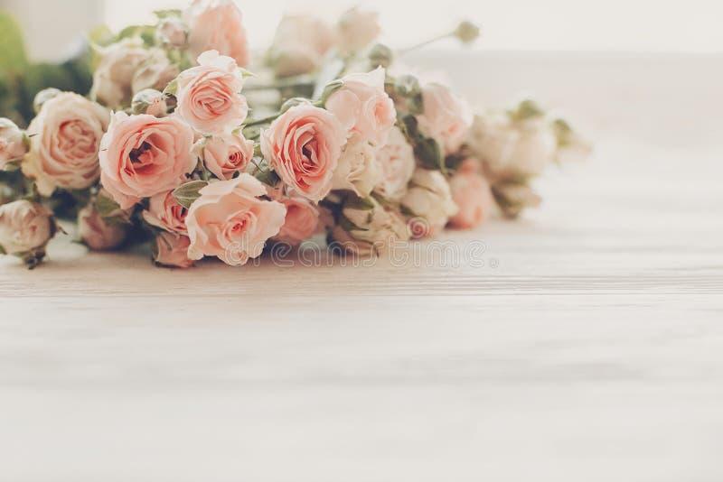 Ρόδινα μικρά τριαντάφυλλα στο ξύλινο υπόβαθρο στο φως, διάστημα για το κείμενο στοκ φωτογραφία