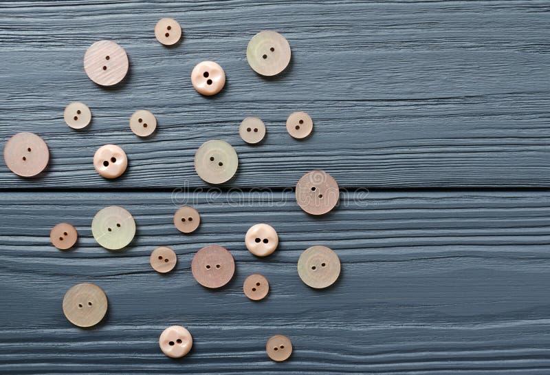 Ρόδινα πλαστικά κουμπιά στο γκρίζο ξύλινο υπόβαθρο στοκ εικόνα