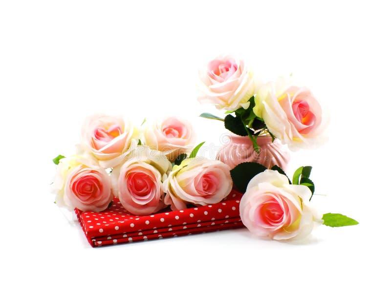 Ρόδινα τεχνητά λουλούδια τριαντάφυλλων και κόκκινο ύφασμα στοκ εικόνες με δικαίωμα ελεύθερης χρήσης