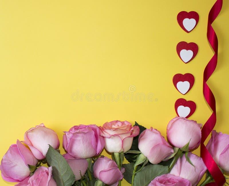 Ρόδινα τριαντάφυλλα, κόκκινες και άσπρες καρδιές και κόκκινη κορδέλλα στο κίτρινο υπόβαθρο Ανασκόπηση ημέρας βαλεντίνων στοκ εικόνα
