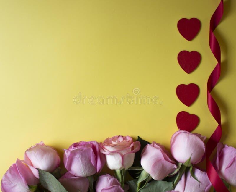 Ρόδινα τριαντάφυλλα, κόκκινες καρδιές και κόκκινη κορδέλλα στο κίτρινο υπόβαθρο Ανασκόπηση ημέρας βαλεντίνων στοκ φωτογραφίες