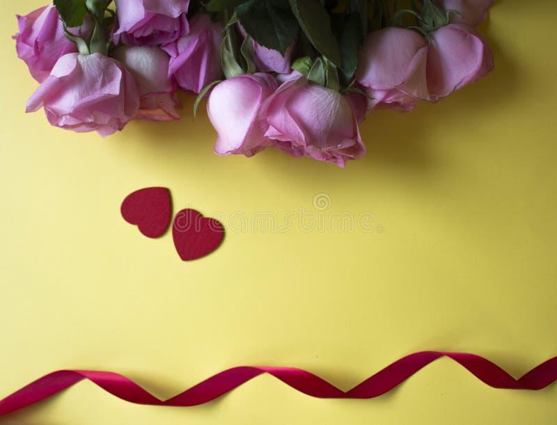 Ρόδινα τριαντάφυλλα, κόκκινες καρδιές και κόκκινη κορδέλλα στο κίτρινο υπόβαθρο Ανασκόπηση ημέρας βαλεντίνων στοκ φωτογραφία με δικαίωμα ελεύθερης χρήσης