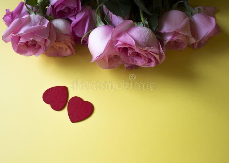 Ρόδινα τριαντάφυλλα, κόκκινες καρδιές στο κίτρινο υπόβαθρο Ανασκόπηση ημέρας βαλεντίνων στοκ φωτογραφίες