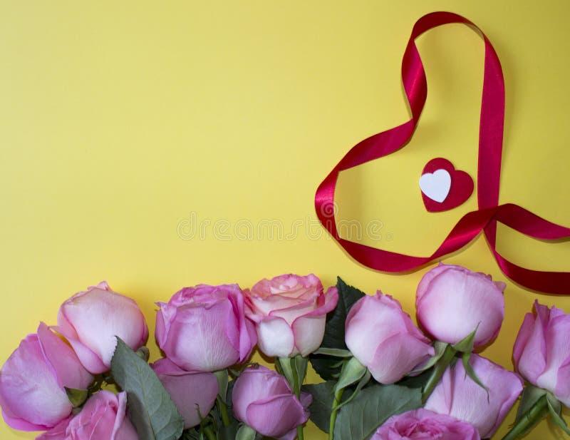 Ρόδινα τριαντάφυλλα, κόκκινη και άσπρη κορδέλλα καρδιών και μορφής καρδιών στο κίτρινο υπόβαθρο στοκ εικόνες