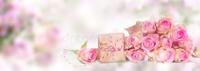 Ρόδινα τριαντάφυλλα με ένα smal δώρο στοκ φωτογραφία με δικαίωμα ελεύθερης χρήσης
