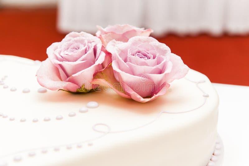 Ρόδινα τριαντάφυλλα φιαγμένα από ζάχαρη στο γαμήλιο κέικ στοκ εικόνα