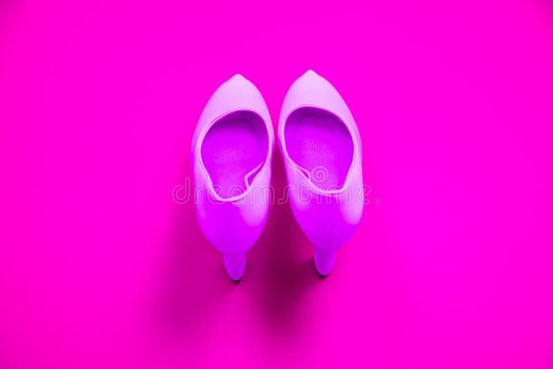Ρόδινα υψηλά βαλμένα τακούνια παπούτσια στο ρόδινο πορφυρό υπόβαθρο - τοπ άποψη - τακούνια που δείχνουν επάνω στοκ φωτογραφία