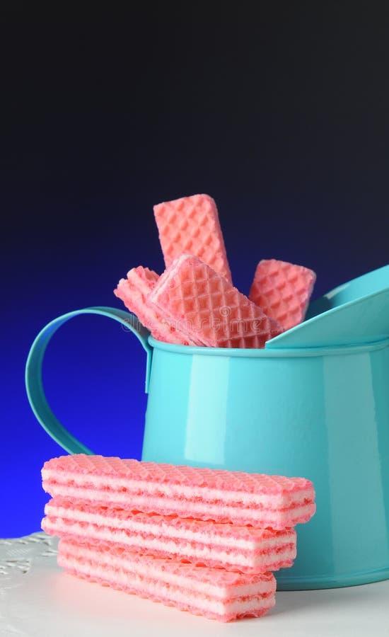 Ρόδινες γκοφρέτες ζάχαρης στον μπλε κασσίτερο στοκ φωτογραφίες