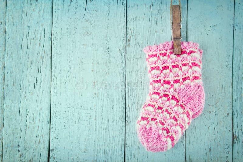 Ρόδινες κάλτσες μωρών σε μια μπλε ξύλινη ανασκόπηση στοκ εικόνα